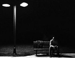 Homem sentado num banco, só e à noite, sob a luz de um poste
